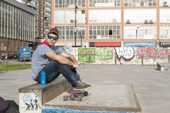 Urban man with blue sunglasses and skateboard sitting on park. Royalty Free Stock Photography