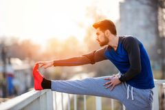 Urban Man Jogger Stretching Leg Outdoors Before Running. Over the bridge. Listening music over headphones stock photography