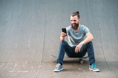 Urban man lifestyle hipster skateboard selfie ramp. Urban man. Leisure and lifestyle. Smiling bearded hipster sitting on skateboard and taking selfie royalty free stock photography