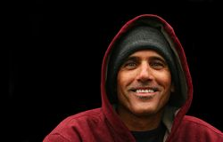 Urban Man Portrait. Portrait of a urban man wearing jacket with hood smiling on black background Stock Photography