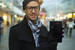 Urban man show tablet computer on street Stock Photo