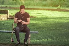 Skater sitting on bench in the park and using smartphone. Urban man sitting on bench in the park and using music app on his smartphone. His skateboard is next to Royalty Free Stock Photo