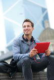 Urban man on tablet sitting in Hong Kong Royalty Free Stock Images
