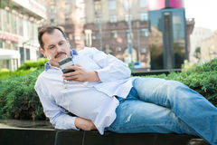 Urban man using smart phone outside using app on 4g wireless dev Royalty Free Stock Photo