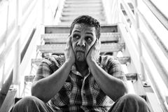 Urban Model 22. Latino background man looking anguished sitting on stairs Royalty Free Stock Images