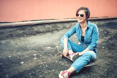 Urban and modern lifestyle, hipster smiling girl with skateboard wearing jeans, sunglasses Stock Images