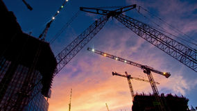 Urban Monsters. Looking up at cranes in an urban development at sunset time stock images