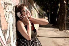 Urban Music. A vintage dressed girl listing to music in a urban environment Stock Photo