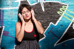 Urban Music. A vintage dressed girl listing to music in a urban environment Stock Images