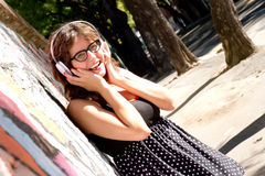 Urban Music. A vintage dressed girl listing to music in a urban environment Royalty Free Stock Photo