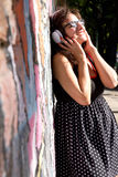 Urban Music. A vintage dressed girl listing to music in a urban environment Stock Photos