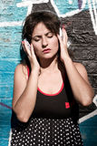 Urban Music. A vintage dressed girl listing to music in a urban environment Stock Photography