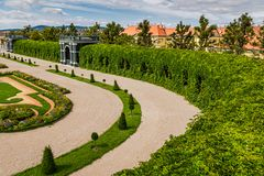 Urban nature: privy garden in majestic Schonbrunn palace, Vienna Austria against orange houses and dramatic sky