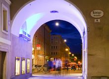 Urban night lights moving people and cars blurred through brightly lit archway Royalty Free Stock Images