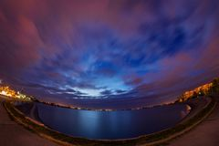 Urban night scene long exposure with clouds on dramatic sky and. Buildings on a lake in Bucharest on Mill Lake Lacul Morii royalty free stock images