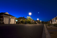 Urban night scene. Showing a road and various houses in a clear sky stock photo