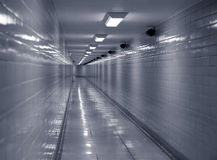 Urban order. Long clean, cold looking corridor lit by fluorescent lights Stock Photo