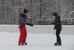 Urban outdoor ice rink in the park. Saint-Petersburg, Russia - December 2, 2016: Urban outdoor ice rink in the park. Two boys are learning to skate Stock Image