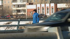 Urban passer. Winter. A man of mature age in a blue warm jacket with the package goes against the backdrop of passing vehicles stock footage