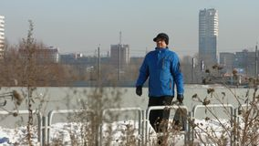 Urban passer. Winter. A man of mature age in a blue warm jacket with the package goes on background of a winter city stock video footage