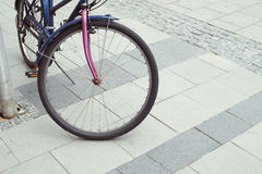 Urban pavement bicycle. Urban pavement background with focus on front wheel of vintage bicycle royalty free stock image