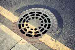 Urban pavement and sewer manhole cover Royalty Free Stock Image