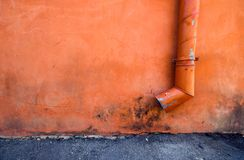 Urban pipe. A drain pipe on an orange wall Royalty Free Stock Photo