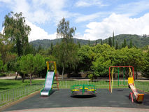 Urban playground, green trees on the lawn, blue sky with white clouds. Urban playground, swings, carousel and small slide, green grass and trees around Stock Photo