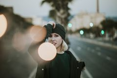 Urban portrait of blonde woman with a knit hat in the middle of the street with lights. Young white woman urban portrait with light flares stock photo