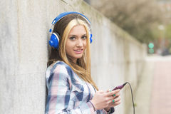 Urban portrait cheerful beautiful girl listen music with headpho Stock Photo