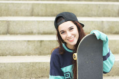 Urban portrait of cheerful young woman with skateboard. Stock Image