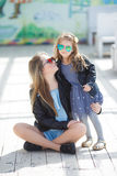Urban portrait of happy mother with little daughter Stock Photos