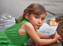 An urban portrait of a little girl near the granitic parapet wall of a fountain Stock Photography