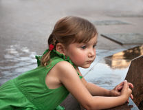 An urban portrait of a little girl near the granitic parapet wall of a fountain Royalty Free Stock Images