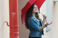 Urban portrait of pedestrian girl carrying plain red umbrella standing with palm up outstretched arm Royalty Free Stock Photo