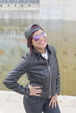Urban portrait of smiling fashion latin woman with sunglasses and baseball cap. Royalty Free Stock Image