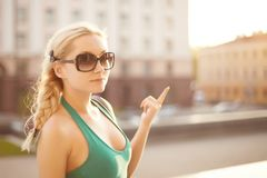 Urban portrait of stylish happy model blonde girl in green dress and sunglasses with hair plaited in a braid posing at royalty free stock images