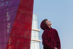 Urban portrait of teenage boy wearing maroon hooded sweatshirt  at modern glass skyscraper city background Stock Image