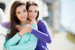 Urban portrait of two beautiful girlfriends. Royalty Free Stock Photo