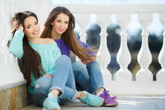 Urban portrait of two beautiful girlfriends. Royalty Free Stock Images