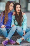 Urban portrait of two beautiful girlfriends. Stock Image