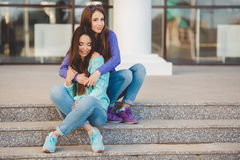 Urban portrait of two beautiful girlfriends. Royalty Free Stock Photography