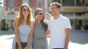 Urban Portrait of Two Cute Women with Long Hair, Sunglasses and Short Dresses Having Fun Together with Handsome Man in. White Shirt in Old City Center During stock video footage