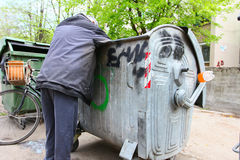 Urban Poverty. A homeless man looking for food in a garbage dumpster Royalty Free Stock Images