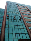 Urban Rappelling. Three men rappelling down a modern skyscraper, for industrial or commercial purposes. Also known as abseiling Stock Photo