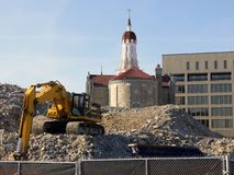 Urban renewal: church and excavator. Excavator and demolition pile in front of historic church in Worcester, Massachusetts Stock Photos
