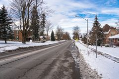 Urban Road Cleared of Snow. Street Cleared of Snow in a Residentian District under Blue Sky with Clouds on a Winter Day. Shelburne, ON, Canada stock photos