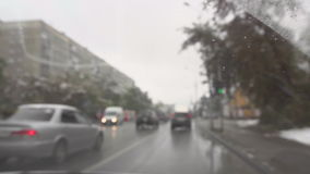 In urban road on a cloudy autumn snowy day. Cars on the streets of Novosibirsk, early snow in October, focus on car windshield, slow motion stock video