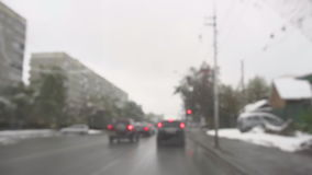 In urban road on a cloudy autumn snowy day. Cars on the streets of Novosibirsk, early snow in October, focus on car windshield, slow motion stock footage