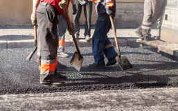 Urban road is under construction, asphalting. In progress, group of workers in uniform with shovels Royalty Free Stock Image